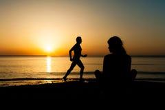 Kontur av kvinnan som håller ögonen på soluppgången arkivbild