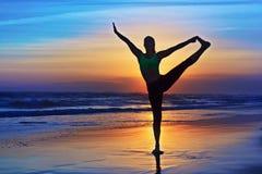 Kontur av kvinnan som sträcker på yogareträtt på solnedgångstranden Arkivfoto