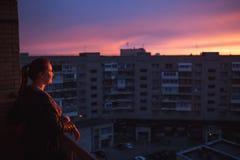 Kontur av kvinnan som tycker om stadssikten på solnedgång Begrepp av ensamhet, evighet, val royaltyfri foto