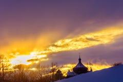 Kontur av kyrkan i den ukrainska byn på solnedgången i vinter arkivfoton