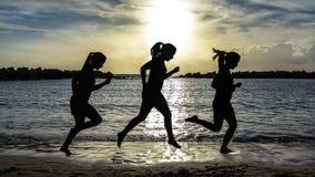 Kontur av löparekvinnan som kör på stranden på solnedgången arkivbilder