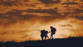 Kontur av laget p? maximumet av berget Sport och aktivt liv av den folkmannen och flickan Teamworkparhj?lp stock video