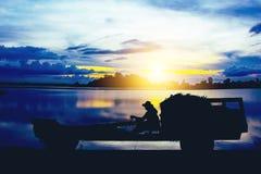 Kontur av lantgårdtraktoren på solnedgång Arkivbilder