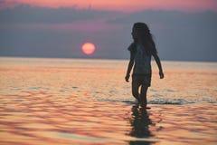 Kontur av lilla flickan mot havet och solnedgången Arkivfoton