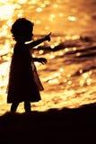 Kontur av lilla flickan som spelar nära havet på solnedgång arkivbilder