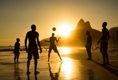 Kontur av lokaler som spelar bollen på solnedgången i den Ipanema stranden, Rio de Janeiro, Brasilien royaltyfri foto