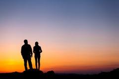 Kontur av lyckafamiljen mot härlig färgrik himmel S Royaltyfria Bilder