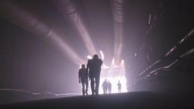Kontur av många byggnadsarbetare som ut går från en stor tunnel lager videofilmer