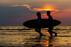 Kontur av man- och flickasurfare som kör till havet med bränning arkivbilder