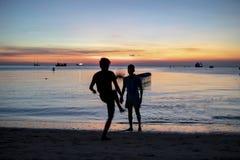Kontur av man som två spelar fotboll på havsstranden mot solar Fotografering för Bildbyråer