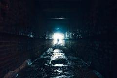 Kontur av mananseendet i mörk underjordisk korridor Ljus på slutet av tunnelbegreppet royaltyfria bilder