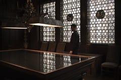Kontur av mananseendet vid en storslagen tabell i ett gammalt hus Blyade fönster som bakifrån låter i ljus honom arkivfoto