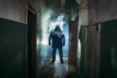 Kontur av mannen i molnet av rök som står i mörk läskig korridor arkivbild