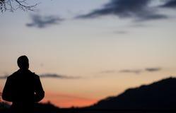 Kontur av mannen i solnedgånghimmel royaltyfri bild