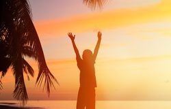 Kontur av mannen med hans händer upp på solnedgången Royaltyfri Foto