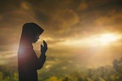 Kontur av mannen med lyftta händer över suddighetskorsbegreppet för Fotografering för Bildbyråer