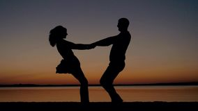 Kontur av mannen och kvinnan på solnedgången av stranden som rymmer händer och att cirkla lager videofilmer