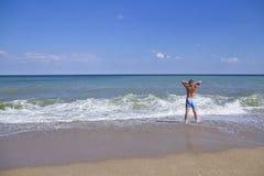Kontur av mannen på havskusten Arkivfoto