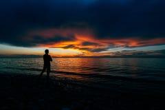 Kontur av mannen på kusten av en sjösolnedgångbakgrund fotografering för bildbyråer
