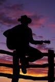 Kontur av mannen på staketet med gitarren arkivfoton