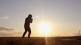 Kontur av mannen som övar thai boxning Konturn av kampsporter man utbildningsboxning på stranden över härlig solnedgångbackgr lager videofilmer