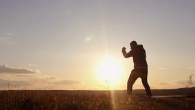 Kontur av mannen som övar thai boxning Konturn av kampsporter man utbildningsboxning på stranden över härlig solnedgångbackgr stock video