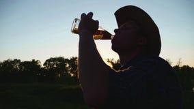 Kontur av mannen som dricker öl under solnedgång stock video