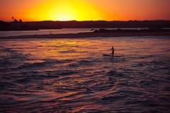 Kontur av mannen som gör rodd på floden under solnedgång royaltyfria foton