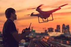 Kontur av mannen som kontrollerar ett surr på solnedgången Stad i bakgrund Fotografering för Bildbyråer