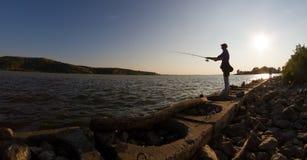 Kontur av mannen som metar på flodkusten Royaltyfria Foton