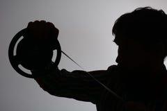 Kontur av mannen som ser på 8mm filmremsa Arkivfoto
