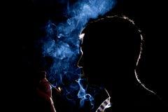 Kontur av mannen som tänder cigaretten i mörkret arkivfoton