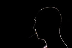 Kontur av mannen som tänder cigaretten i mörkret arkivfoto