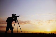 Kontur av mannen som tar foto med hans kamera på solnedgången med en dramatisk himmel royaltyfri foto