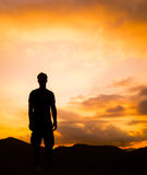 Kontur av mannen som överst står ett ensamt av berget med orange skymning Royaltyfri Foto