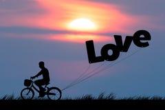 Kontur av manritten på cykeln med luftballonger för att uttrycka FÖRÄLSKELSE på solnedgånghimmel (förälskelsevalentinbegreppet) Royaltyfri Bild