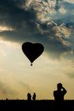 Kontur av manturisten som tar foto av ballongen för varm luft för hjärtaform royaltyfri bild