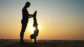 Kontur av modern med att göra för dotter som är gymnastiskt på stranden på solnedgången arkivfilmer