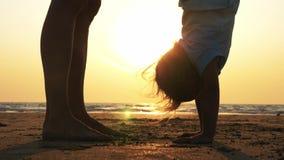 Kontur av modern med att göra för dotter som är gymnastiskt på stranden på solnedgången stock video