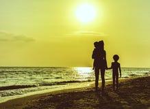 Kontur av modern med barn på stranden i solnedgång royaltyfri bild
