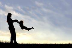 Kontur av modern som spelar med barnet utanför på solnedgången Arkivbild