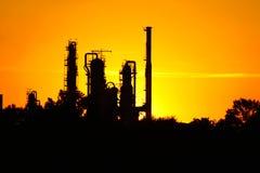 Kontur av oljeraffinaderifabriken mot solnedgång Arkivfoton