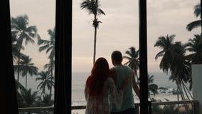 Kontur av par som är förälskade på terrassen som ser havet arkivfilmer