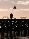 Kontur av par som går på Pier At Dusk Arkivbild