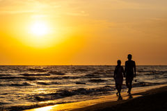 Kontur av par som går på stranden Arkivbild