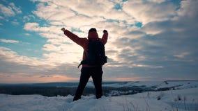 Kontur av personen i berg Ung man med ryggsäckanseende med lyftta händer överst av ett berg Sport och lager videofilmer