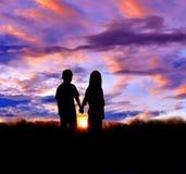 Kontur av pojke- och flickaställningshanden - in - hand som håller ögonen på solnedgången arkivfoton