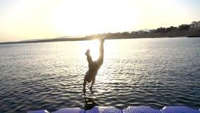 Kontur av pojken som hoppar från pir på solnedgången på havet arkivfilmer