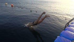 Kontur av pojken som hoppar fr?n pir p? solnedg?ngen p? havet arkivfilmer