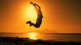 Kontur av pojken som hoppar på soluppgång på stranden arkivfilmer
